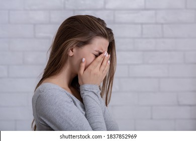 Desperate young woman crying from hopelessness, covering her face with hands, blank space. Depressed millennial lady suffering from PTSD, stress or anxiety. Mental health concept