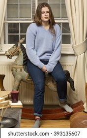 Despondent. A young teenage girl is sitting on her childhood toy, a rocking horse, and thinks through a problem that is worrying her.