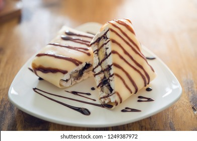 Dessert of banana cold crepe chocolate sauce on white dish.Dessert of banana crepe.Banana Crepe and Chocolate Cheese Dumplings on wooden table .
