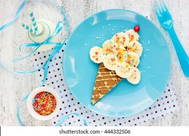 Dessert or breakfast for kids - pancake with banana and colorful sugar sprinkling in the shape of ice cream cone. Creative food art idea for children meal top view