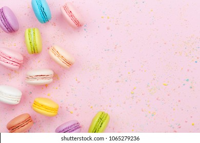 Dessert cake macaron or macaroon on pink background top view. Flat lay composition.