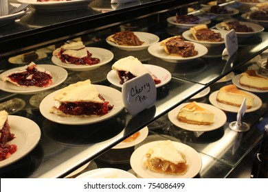 Dessert case of pies with cherry pie sign