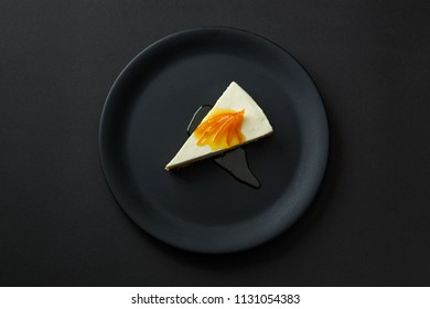 Dessert of cheesecake with jam on a black plate isolated on a black background.