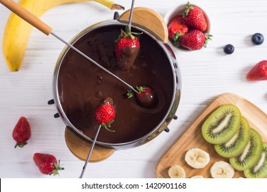 Dessert . Chocolate fondue whith fruit and berries . Food background