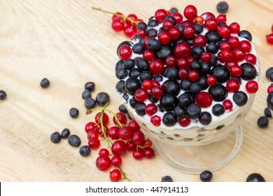 Dessert with cream and fresh berries (red and black currants, blueberry)