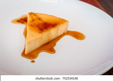 Dessert Flan cheese with caramel on top on a white plate.