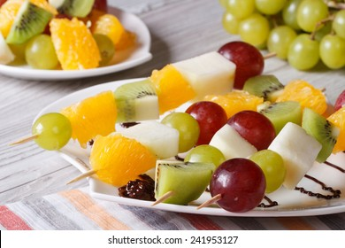 Dessert of fresh fruit on skewers on a white plate close-up. horizontal