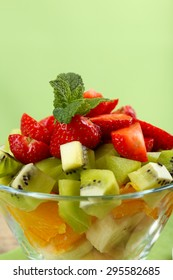 Dessert of fresh fruits in glass saucer on green background