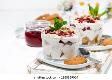 dessert in a glass with biscuits, cream and jam, closeup