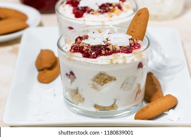 dessert in a glass with cookies, cream and jam, closeup horizontal
