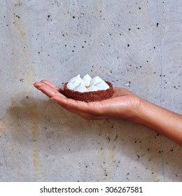 Dessert in a hand on a concrete background with copy space