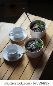 Dessert healthy breakfast of oat pudding in a white keraimic mold. Decorated with sprig of mint and powdered sugar. Two empty cups