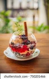Dessert ice cream with berry in glass of jar on the table decorate with cinnamon stick