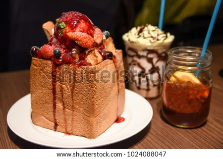 A dessert in japanese is a strawberry honey toast with fruit jar and milk shake