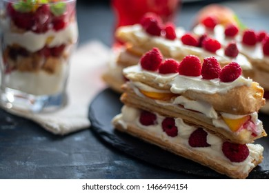 Dessert Milfey. Strips of puff pastry with curd cream raspberry berries and peach slices. In the background, the same, only in a glass. On a dark background.