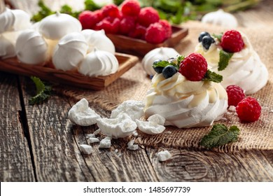Dessert Pavlova with raspberries, blueberries and mint on a old wooden table. Dessert Pavlova and small meringues on a rustic background.