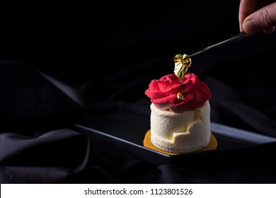 Dessert with red rose flower of cream and edible gold on black background