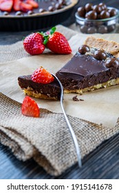 Dessert spoon cutting chocolate tart or pie slice topped with strawberries, chocolate candy and almonds. Selective focus on cake, blurred background. Delicious gluten-free homemade crust or tartlet.