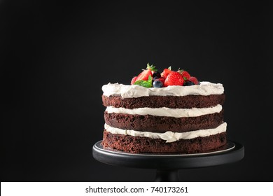 Dessert stand with delicious chocolate cake on black background