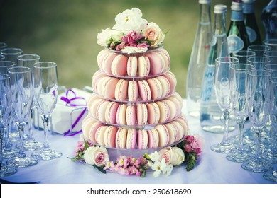 Dessert table with a large macaroons composition - pyramid in pink, decorated with flowers.
