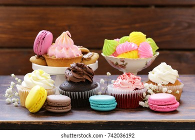 Dessert table - muffins, biscuits, macaroons, capcakes on a wooden background