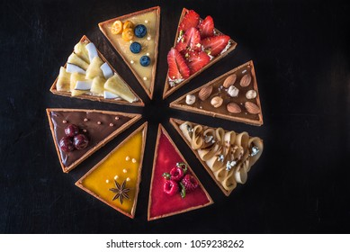 Dessert table is a tart cake with different fillings of fruits, berries, nuts and chocolate close-up. Fresh food cake on a dark background top view.