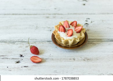 Dessert tartlets with butter cream and fresh strawberries on white wooden background. Horizontal orientation
