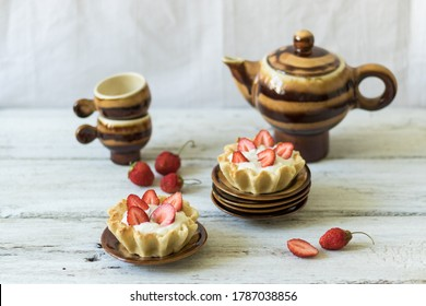 Dessert tartlets with butter cream and fresh strawberries on a white wooden background. Ceramic tableware for saina or coffee ceremony. Horizontal orientation