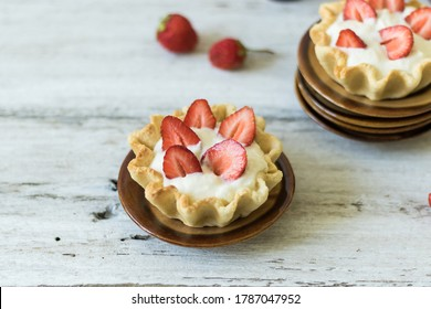 Dessert tartlets with butter cream and fresh strawberries on a white wooden background. Sweets for tea drinking. Horizontal orientation