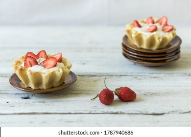 Dessert tartlets with butter cream and fresh strawberries on a white wooden background. Sweets for tea drinking