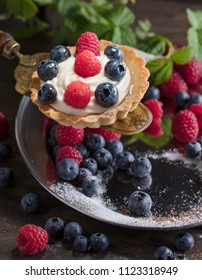 Dessert tarts with raspberries and blueberries on a wooden table. Closeup of fancy gourmet fresh berry dessert tarts.