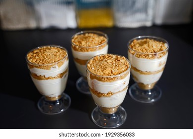 Dessert with yogurt, cottage cheese, tangerines, cookies and cream arranged in glasses.
