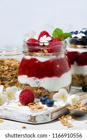 desserts with muesli, berry and fruit puree in jars on white table, closeup