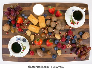 Desserts, two cups of coffee, fruit and nuts.