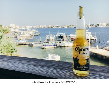 DESTIN, FL, USA - SEPTEMBER 28TH, 2016: A bottle of Corona beer placed on a wooden ledge with a lime against blurred harbor background. Corona is one the most popular imported beer brands.