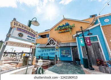 Destin, USA - April 24, 2018: Harborwalk during sunny day in Florida panhandle gulf of mexico, Margaritaville restaurant, bar at marina, wharf seaside