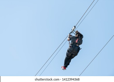 Destin, USA - April 24, 2018: Back of one young African american woman isolated against blue sky on zipline or zip line in attraction park in Florida Panhandle