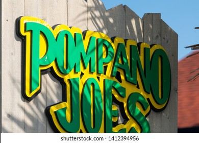 Destin, USA - April 24, 2018: Sign for Pompano Joes seafood restaurant eatery in Miramar Beach attached to fence in Florida