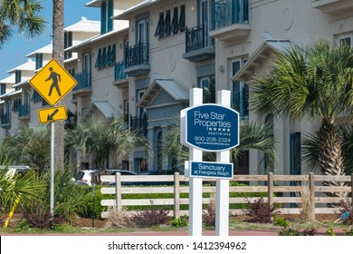 Destin, USA - April 24, 2018: Real estate sign for Five star properties of Sanctuary, Frangista Beach, Miramar city with apartment buildings, townhouse and palm trees in Florida panhandle