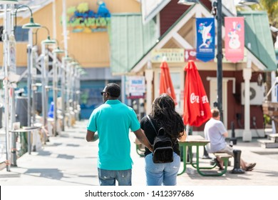 Destin, USA - April 24, 2018: City town Harborwalk village boardwalk at marina with Margaritaville and couple walking on sunny day in Florida Panhandle, Gulf of Mexico