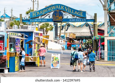 Destin, USA - April 24, 2018: Sign for Harborwalk Village in Emerald Grande Coast in Florida Panhandle with people walking and shopping, buying food in cafe, street vendor restaurants