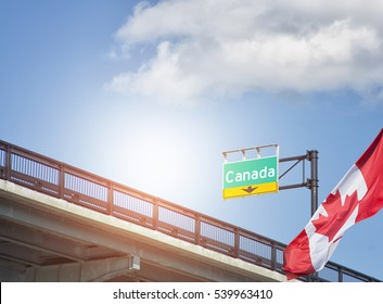 Destination Canada sign on highway with Canadian flag waving beside