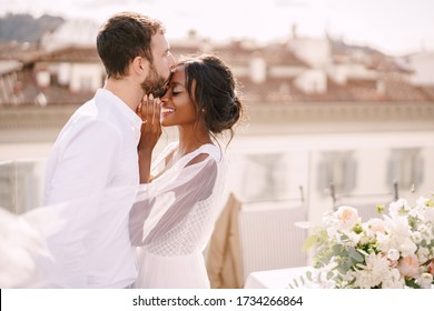 Destination fine-art wedding in Florence, Italy. Caucasian groom and African-American bride cuddling on a rooftop in sunset sunlight. Multiracial wedding couple