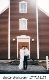 Destination Iceland wedding. Wedding couple in front of a black church. The groom hugs the bride.