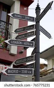 destination road signs on pillar