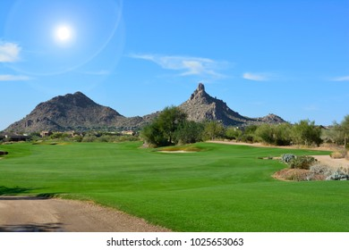 Destination scenic - Green grass golf course fairway landscape with mountains, blue sky, white clouds, and sun shining during the day