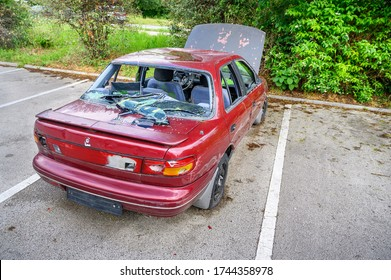 Destroyed abandoned car with broken car glasses, flat tires and open hood