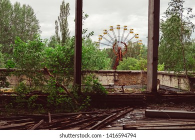 Destroyed abandoned ghost city Pripyat ruins after Chernobyl disaster. Old broken rusty metal yellow carousel wheel , amusement park. Exclusion zone, radiation risk, apocalyptic fallout lost town.