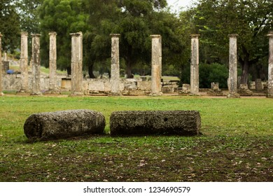 destroyed ancient marble colonnade ruins with falling park of columns and old alley way on background in park outdoor garden nature place in raining time