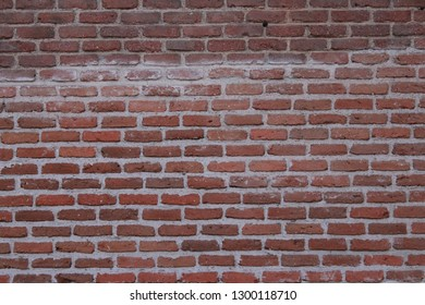 Destroyed brick wall, red texture, background.